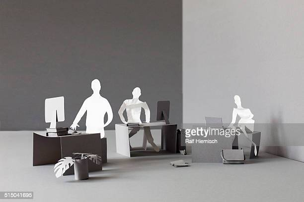 Paper businessmen working at desks in office