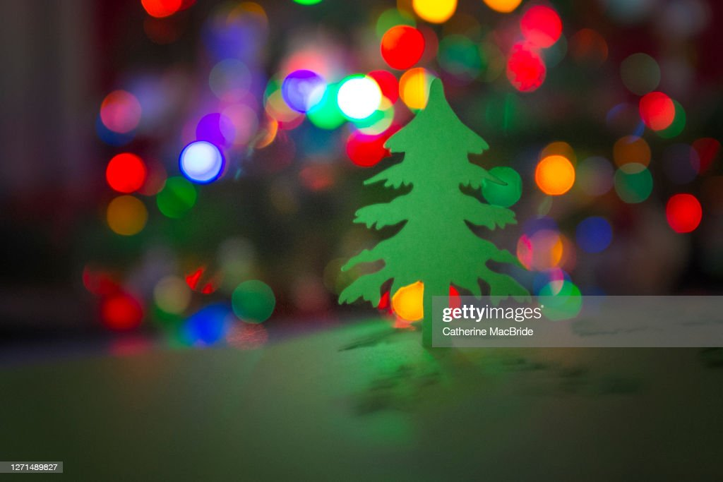 Paper Christmas Tree Cut-Out In Front Of Christmas Tree Lights : Stock Photo