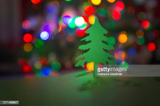 paper christmas tree cut-out in front of christmas tree lights - catherine macbride stock pictures, royalty-free photos & images