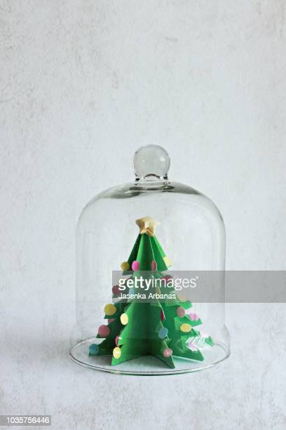 A paper Christmas tree under a bell-jar