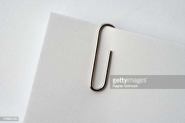 paper clip on corner of paper - paper clips stock photos and pictures