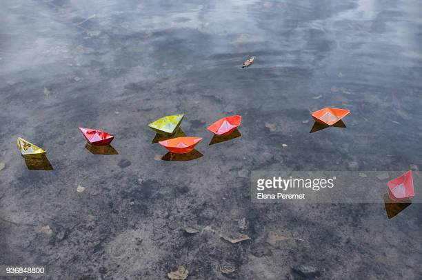 Paper colorful boats float on the water