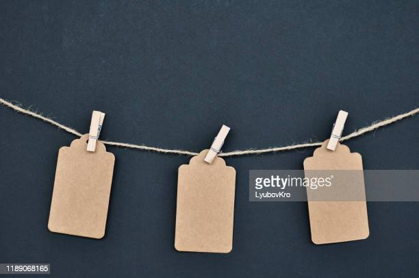 paper craft discount labels are attached with clothespins to the rope on a black background. - clothespin stock pictures, royalty-free photos & images