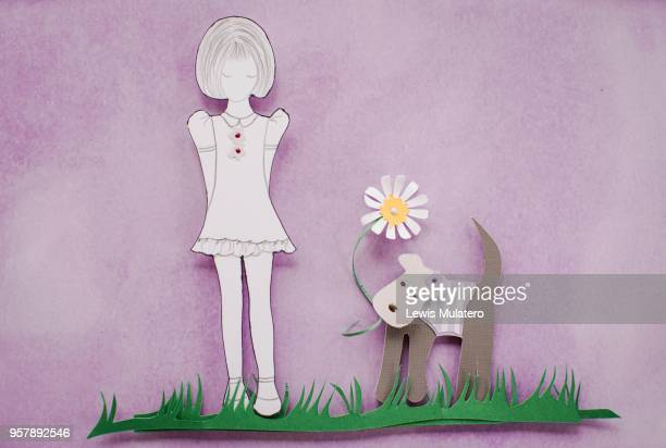Paper craft of girl and dog holding a daisy