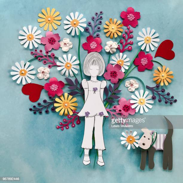 Paper craft picture of a girl holding a large bouquet of flowers behind her back with a little dog standing next to her with a daisy in its mouth