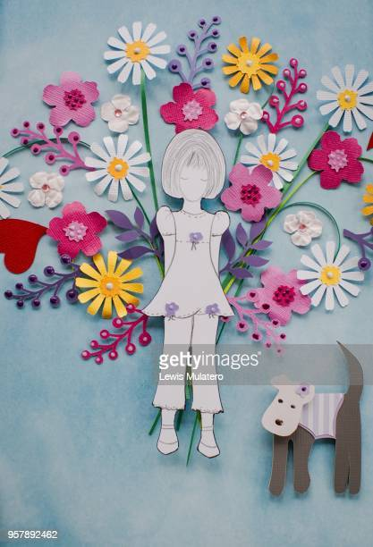 Paper craft picture of a girl holding a large bouquet of flowers behind her back and a little dog next to her