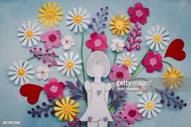 Paper craft picture of a girl holding a large bouquet of flowers behind her back