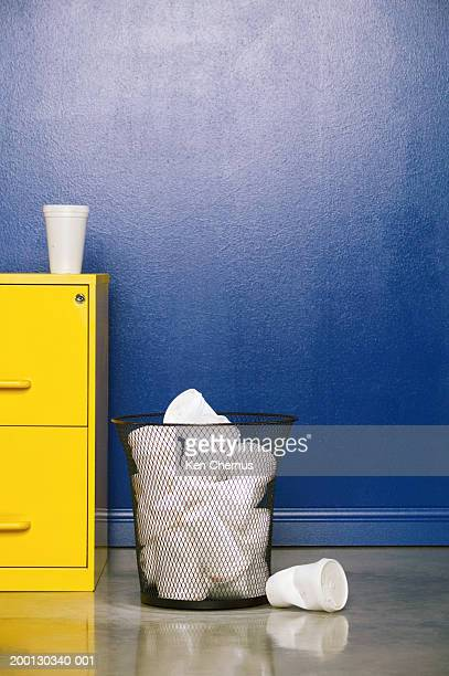 Paper cup sitting on file cabinet next to full trash bin