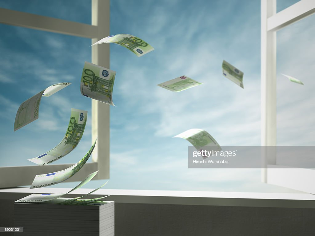 Paper currency blowing out of open window : Stock Photo