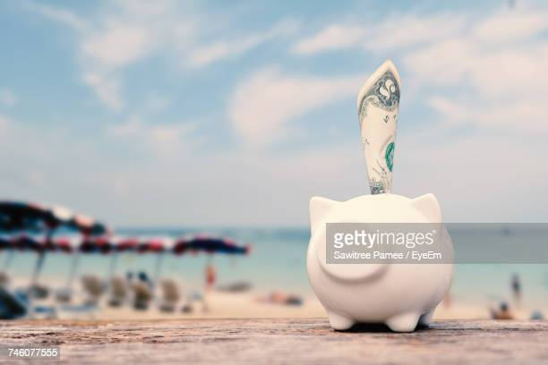 Paper Currency In Piggy Bank On Table At Beach Against Sky