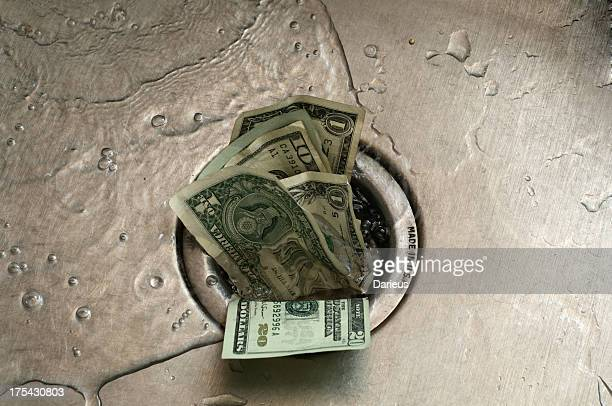 US paper currency, shoved in to the drain of a wet sink