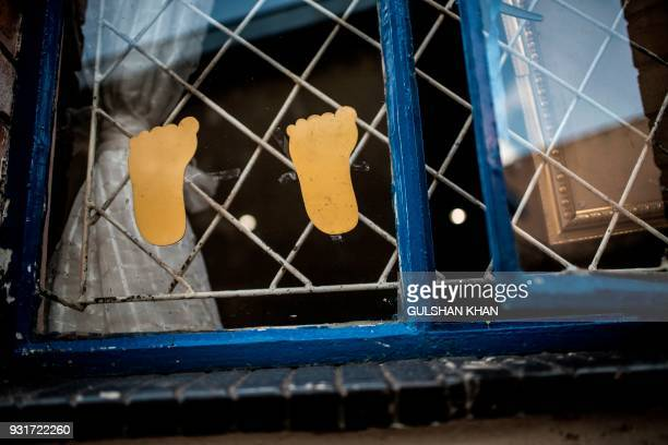 TOPSHOT Paper cutouts are pictured on a window inside the Childcare Orientation Centre in Klipspruit West in Soweto on March 13 2017 Nine children...