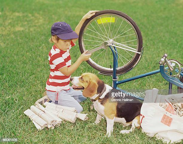 Paper delivery boy with dog fixing bicycle