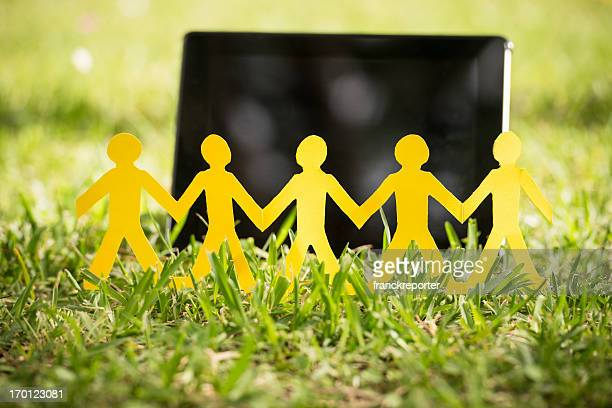 paper doll family with tablet on the grass