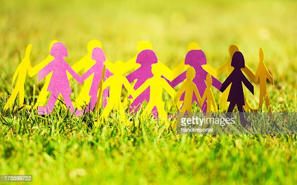Paper doll on the grass like a community -  Teamwork