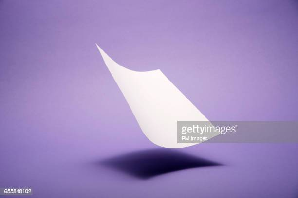 paper falling onto purple background - purple background stock photos and pictures