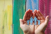 Paper family in hands on wooden coloured background welfare concept