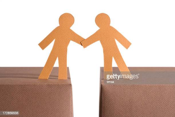 Paper figures with a gap between them holding hands on boxes