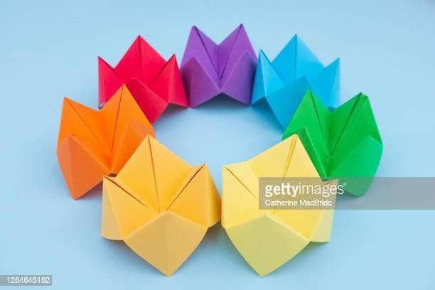 paper fortune tellers arranged by colour on a blue background - catherine macbride stock pictures, royalty-free photos & images