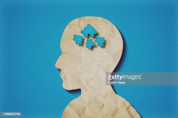 paper head with puzzle pieces-autism concept.blue background - smart stock pictures, royalty-free photos & images