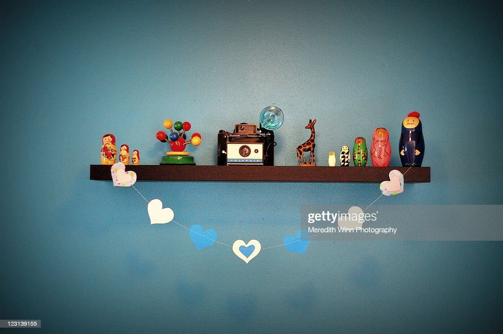 Paper hearts strung on shelf of collectibles : Stock Photo