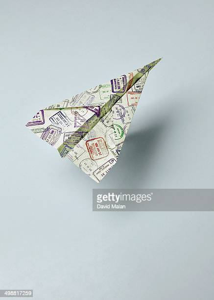 Paper jet covered with passport stamps