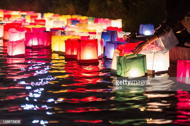 Paper lantern floats are released into the water during a ceremony for the victims of the atomic bomb in Hiroshima at Ibirapuera park in Sao Paulo...
