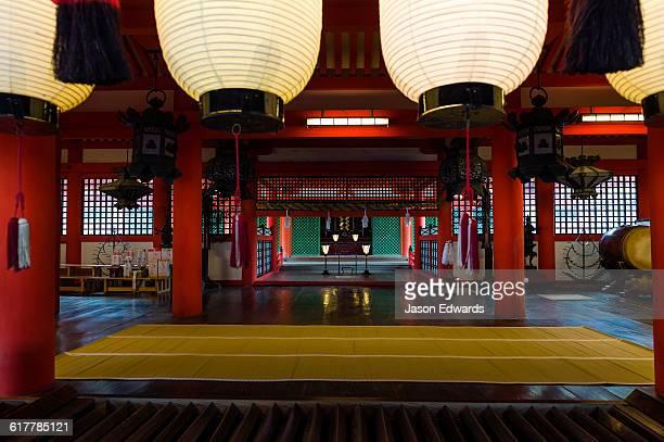 Paper lanterns above tatami matts in the tranquil Itsukushima Shrine.