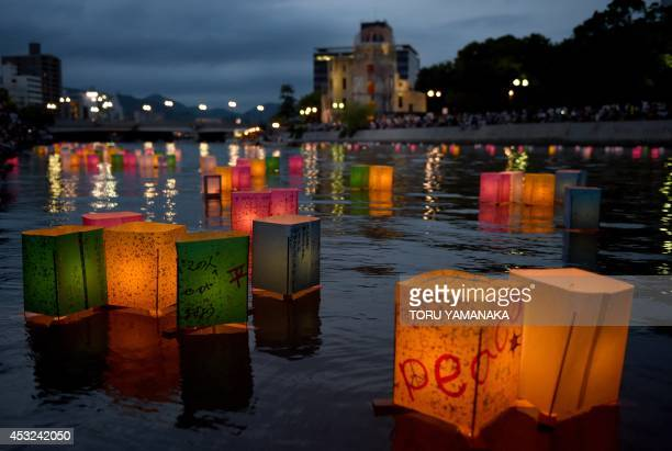 Paper lanterns float in the Motoyasu River in front of the Atomic Bomb Dome at the Peace Memorial Park in Hiroshima on August 6 2014 The Japanese...