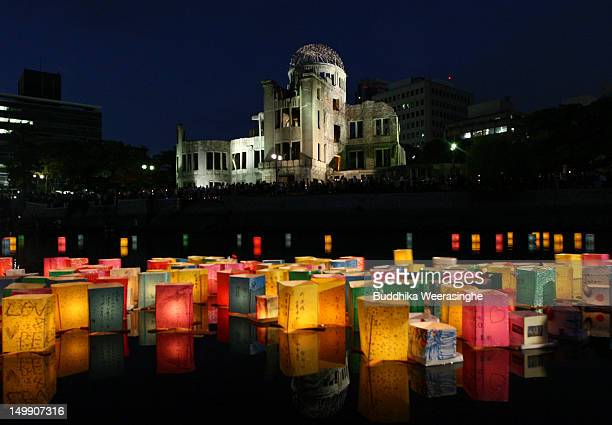 Paper lanterns float on the Motoyasu River in front of the Hiroshima Peace Memorial commonly called the Atomic Bomb Dome at the Hiroshima Peace...
