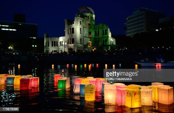 Paper lanterns lit in rememberance for victims of the 1945 atomic bombing of Hiroshima float on the Motoyasu River in front of the Atomic Bomb Dome...