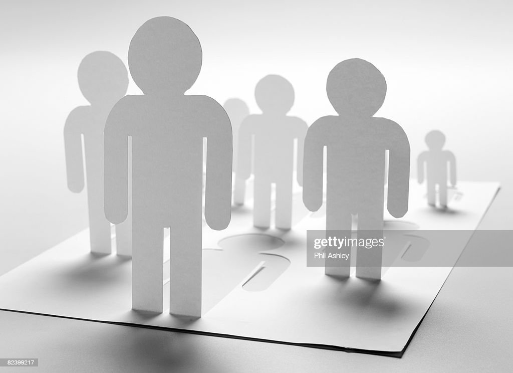 paper man cut out standing in front of the group : Stock Photo
