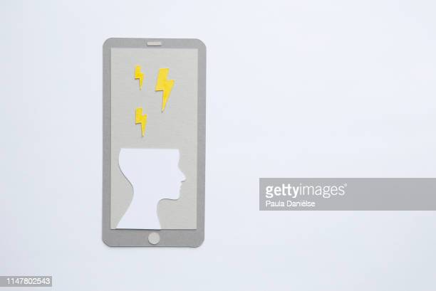 paper mobile phone with human head and lightning - mental wellbeing stock pictures, royalty-free photos & images