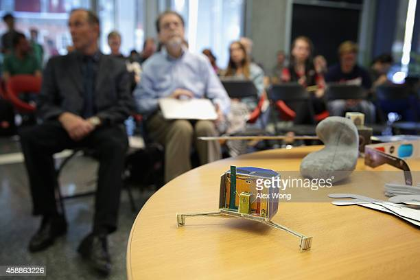 A paper mockup of spacecraft Rosetta and the 3D print out of the comet it's landing on are seen during a landing viewing party November 12 2014 at...