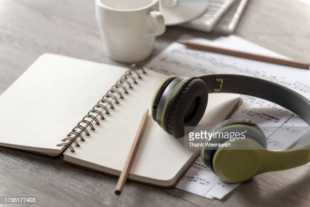 paper notebook, pencil and earphone with note music paper on the table,music writer concept, song writer, - author stock pictures, royalty-free photos & images