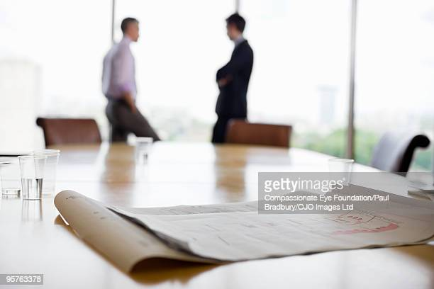 Paper on table with business people in background