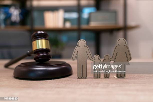 paper people chain, books and judge's gavel. law, family politics and marriage legalization. - adoptie stockfoto's en -beelden