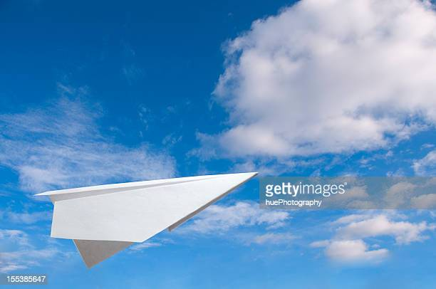 Paper plane flying in the air against a blue sky