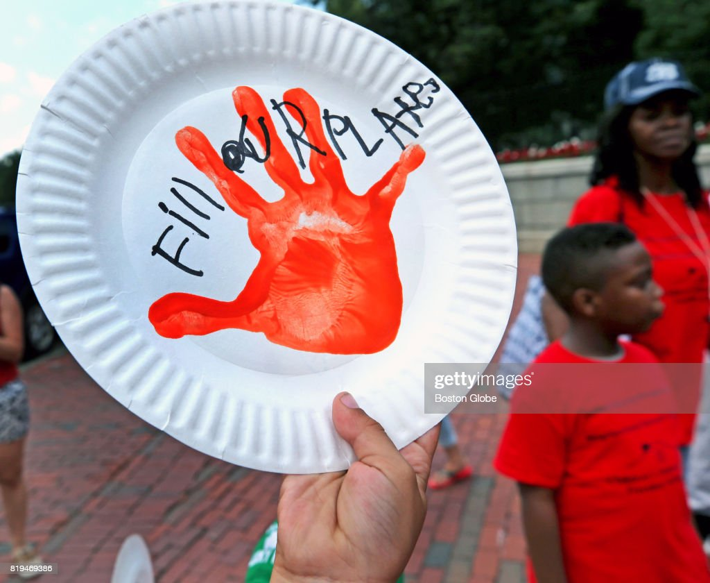 A paper plate is held up at the front steps of the Massachusetts State House in & Young People March Against Child Hunger Pictures | Getty Images