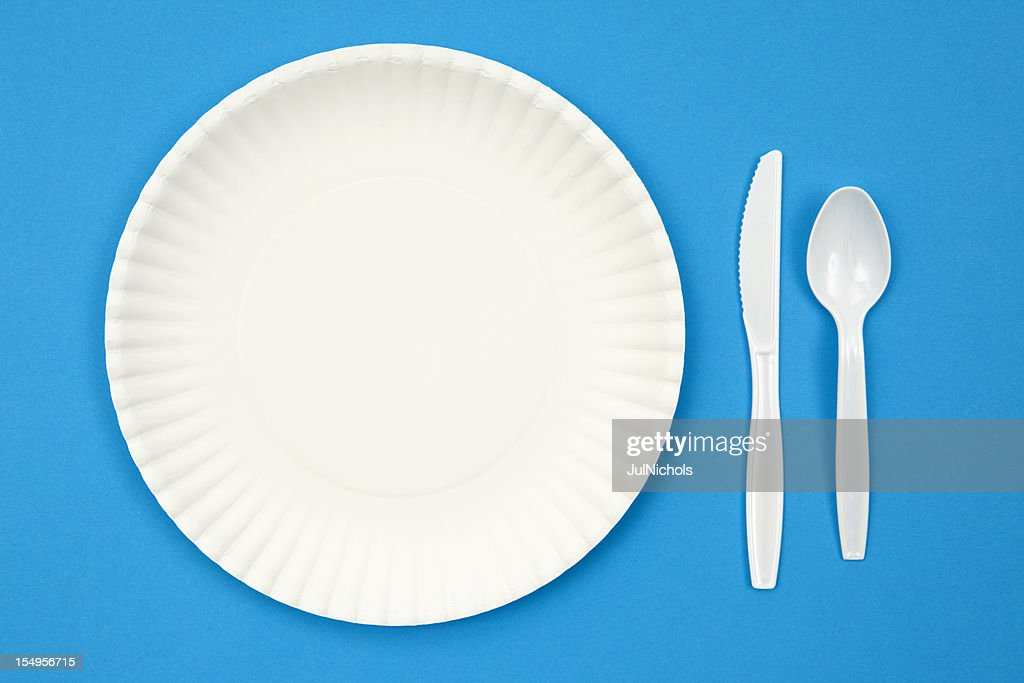 A paper plate next to plastic utensils on a blue table : Stock Photo