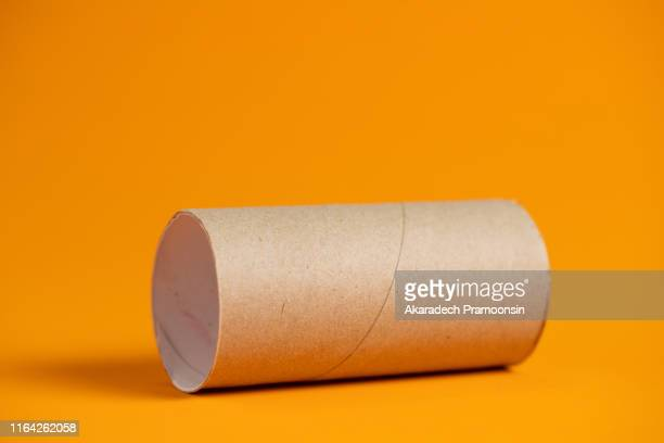 paper roll on orange background. - toilet paper stock pictures, royalty-free photos & images
