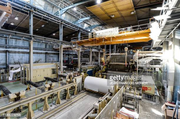 A paper rolling machine is pictured in the empty at the Arjowiggins paper mill factory in BessesurBraye on March 27 2019 as employees gather outside...