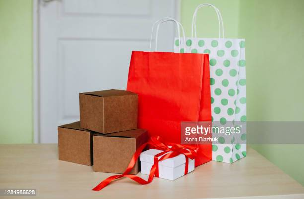 paper shopping bags and boxes at home. concept of black friday, cyber monday, online shopping, gifts and packages. - cyber monday stock pictures, royalty-free photos & images