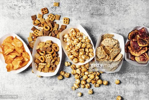 paper trays with caramelized popcorn, chips, and snack mix on gray background - cracker snack stock pictures, royalty-free photos & images