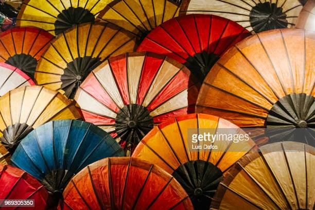 paper umbrellas at luang prabang night market - commercial event stock photos and pictures