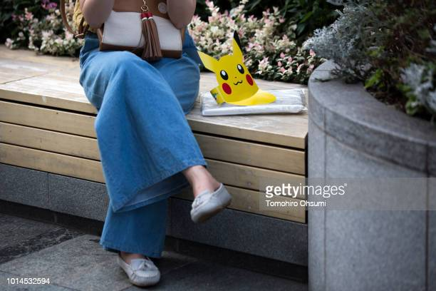 A paper visor of Pikachu a character from Pokemon series game titles is seen next to a woman sitting on a bench during the Pikachu Outbreak event...