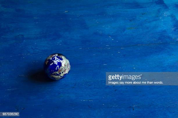 a paper weight in planet earth style on blue background. - country geographic area stock pictures, royalty-free photos & images