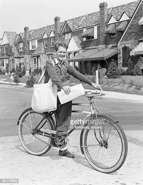 Paperboy on bicycle in suburban neighborhood, with sack over shoulder and folded newspaper in hand. (Photo by H. Armstrong Roberts/Retrofile/Getty Images)