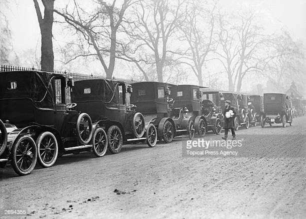 A paperboy passes taxicabs awaiting customers at a rank in London's Knightsbridge