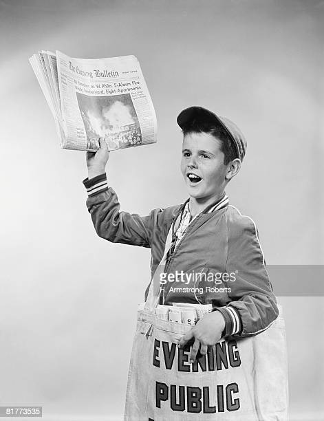 Paperboy selling newspapers, holding paper up in one hand, with bag of papers over shoulder, Philadelphia, Pennsylvania, USA. (Photo by H. Armstrong Roberts/Retrofile/Getty Images)